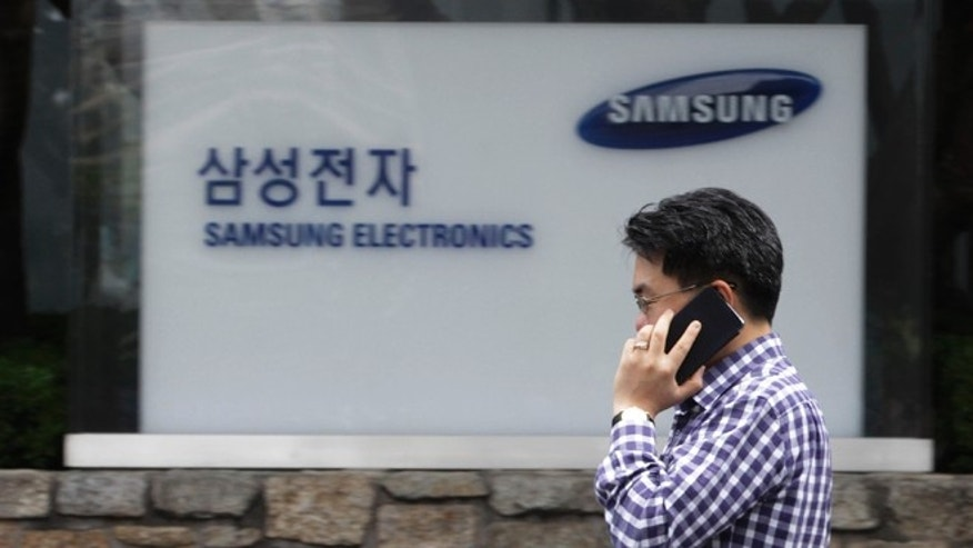 Aug. 24, 2012: A man walks by Samsung Electronics Co.'s headquarters in Seoul, South Korea. The Seoul Central District Court ruled Friday that technology rivals Apple Inc. and Samsung Electronics Co. both infringed on each other's patents.