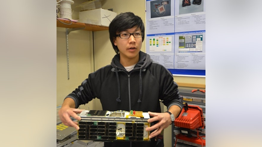A student holds CINEMA, the CubeSat for Ions, Neutrals, Electrons & MAgnetic fields, an 8-pound, shoebox-size package. A similar type CubeSat could carry out lunar exploration in the future.