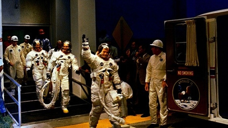 The Apollo 11 crew leaves Kennedy Space Center's Manned Spacecraft Operations Building during the pre-launch countdown. Mission commander Neil Armstrong, command module pilot Michael Collins, and lunar module pilot Buzz Aldrin prepare to ride t