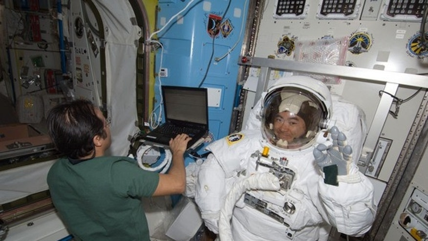 Japanese astronaut Akihiko Hoshide of JAXA waves while testing his spacesuit inside the International Space Station ahead of an Aug. 30, 2012 spacewalk with crewmate Sunita Williams of NASA. NASA astronaut Joe Acaba (left) assists.