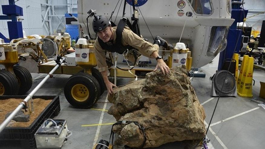 Marc Reagan is suspended above a boulder on a simulated asteroid inside NASA Active Response Gravity Offload System, or ARGOS, at Johnson Space Center in Houston, Aug. 30, 2012
