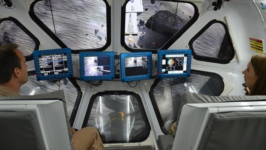 : Scientist Liz Rampe and flight controller David Coan pilot NASA's multi-mission Space Exploration Vehicle (SEV) during an asteroid mission simulation at the Johnson Space Center in Houston, Aug. 30, 2012.