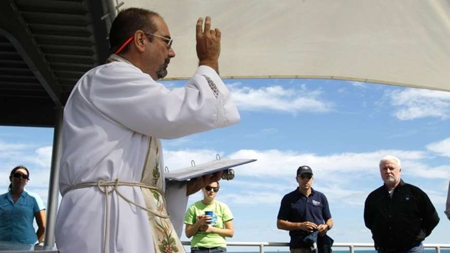Sept. 10, 2012: Aboard the RV Manta, Father Stephen Duncan, left, conducts a memorial service in the Gulf of Mexico off the Texas Coast Monday for the two men who died aboard the USS Hatteras in 1863 during the Civil War. The service was held at the site of the shipwreck where researchers are making a 3-D map using sonar equipment.