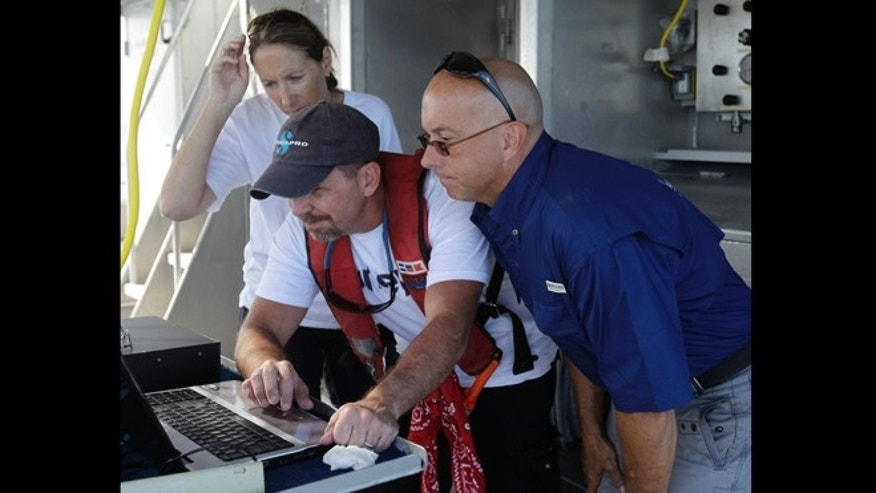 Sept. 10, 2012: Project coordinator Emma Hickerson, left, marine archeologist Christopher Horrell, center, and Capt. Darrell Walker look at a sonar image as they search for the wreckage of the USS Hatteras.