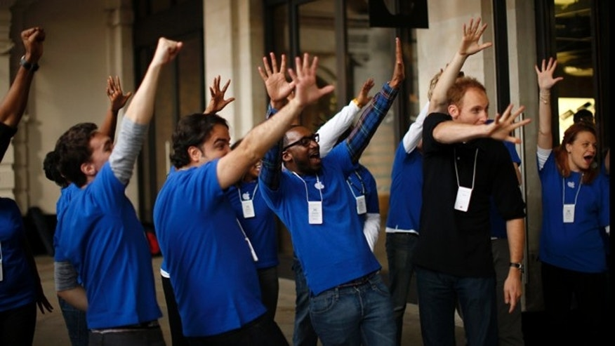 Sept. 21, 2012: Apple workers gesture with five fingers at customers leaving their store after purchasing iPhone 5 handsets in Covent Garden, London. The smartphone is being launched in the U.S., Britain, Canada, France and Germany. It will go on sale in 22 more countries a week later.