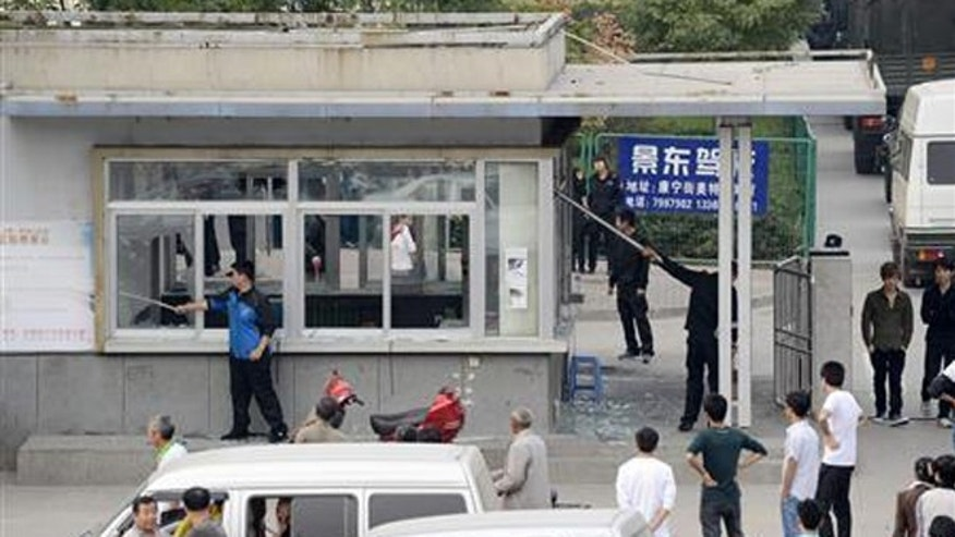 Sept. 24, 2012: Workers clean up glass shards from the broken windows of a security room near paramilitary police vehicles parked near an entrance of a Foxconn Tech-Industry park in Taiyuan, Shanxi province.