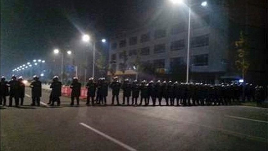 Sept. 24, 2012: Police in anti-riot suits cordon off a road near Foxconn's plant in Taiyuan, capital of Northern China's Shanxi province, in this cellphone picture. The company that makes Apple's iPhones suspended production at a factory in China on Monday after a brawl by as many as 2,000 employees at a nearby dormitory injured 40 people.
