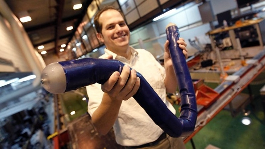 Oct. 2, 2012: Brandon Taravella, assistant professor of naval architecture and marine engineering, handles a prototype robotic eel that might be able to wriggle through dangerous waters with almost no wake, letting it move on little power and with little chance of radar detection as it looks for underwater mines.