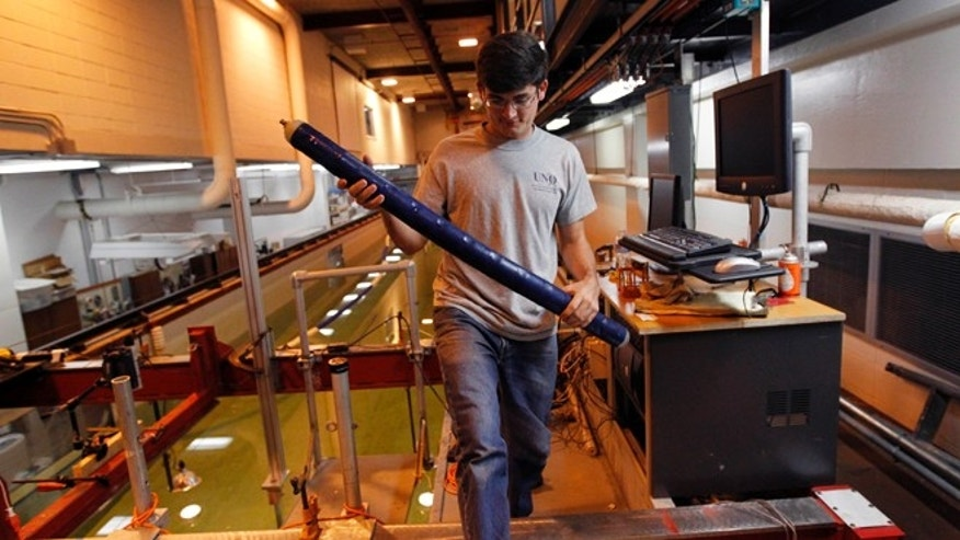 Oct. 2, 2012: Graduate student Baker Potts handles a prototype robotic eel inside the engineering building at the University of New Orleans.