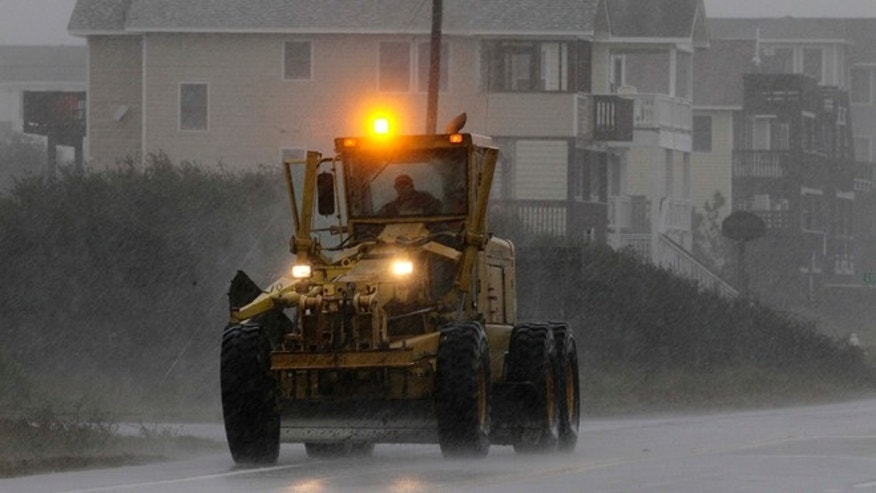Oct. 28, 2012: Earth-moving equipment drives south along Virginia Dare Trail in the rain and wind generated by Hurricane Sandy in Kill Devil Hills, N.C., as the storm moves up the East Coast.