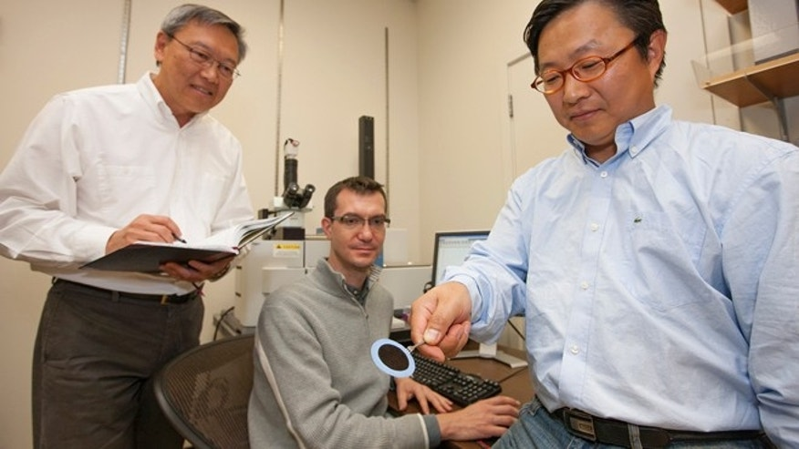 From left, Kuang Jen Wu and Francesco Fornasiero look on as Sangil Kim holds a piece of the nanotube fabric that repels chemical and biological agents.