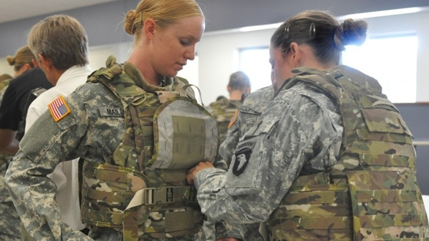 Aug. 21, 2012: Spc. Arielle Mailloux gets some help adjusting her protoype Generation III Improved Outer Tactical Vest from Capt. Lindsey Pawlowski at Fort Campbell, Ky.