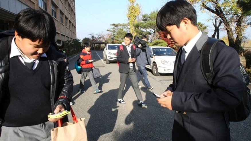 Nov. 9, 2012: South Korean students check their smartphones after classes at Bibong Middle School in Hwaseong, South Korea. Students agreed to hand in their smartphones when they arrive at school in the morning and get them back when they leave for home after classes.