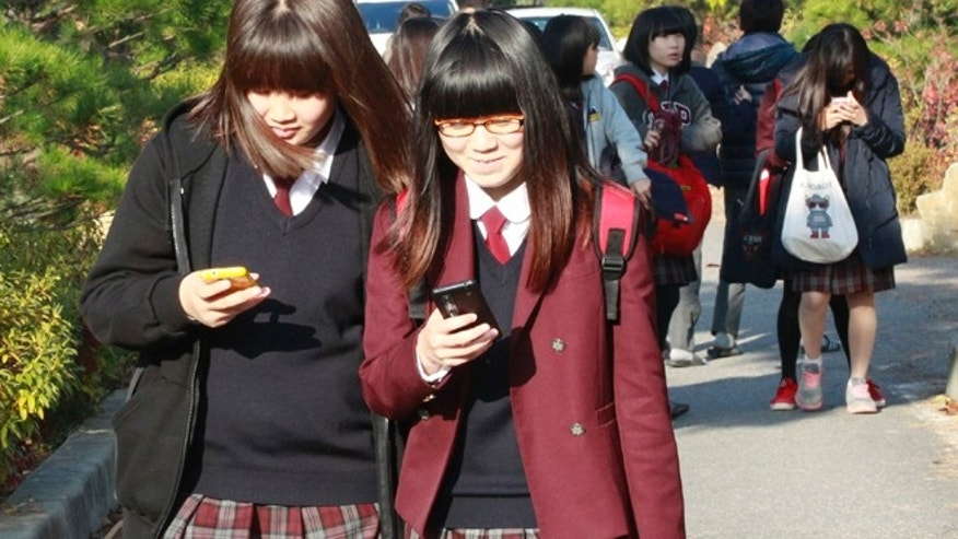 Nov. 9, 2012: South Korean students check their smartphones after classes at Bibong Middle School in Hwaseong, South Korea. Across the entire population, South Koreas government estimated 2.55 million people are addicted to smartphones.