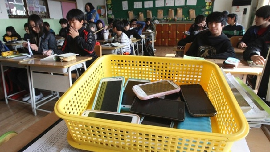 Nov. 9, 2012: Smartphones collected from students are placed in a plastic basket during a class at Chilbo elementary school in Suwon, South Korea.