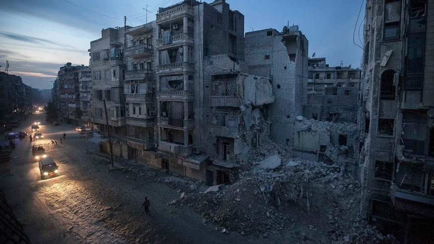 Nov. 29, 2012: Night falls on a Syrian rebel-controlled area as destroyed buildings, including Dar Al-Shifa hospital, are seen on Sa'ar street after airstrikes targeted the area last week, killing dozens.