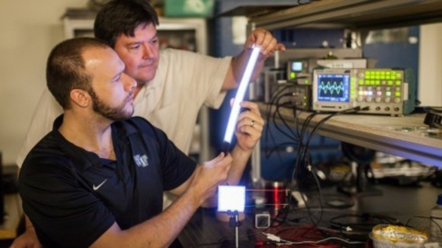 Researchers have made a new glowing plastic material that they've formed into lights of different shapes. Here, physicist David Carroll (front) and graduate student Greg Smith (behind) with a few of their creations.