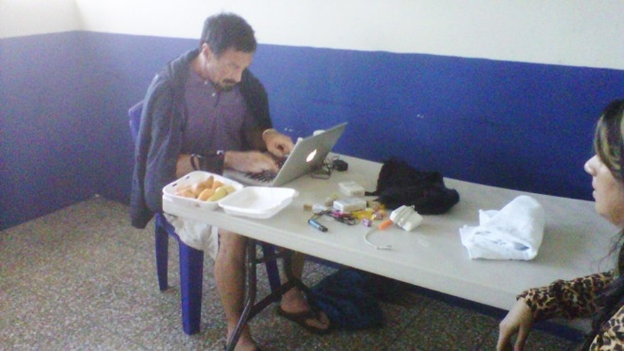 Dec. 6, 2012: John McAfee updates his blog at an immigration detention center in Guatemala City. The anti-virus guru was arrested at a hotel in an upscale neighborhood with the help of Interpol agents. Guatemalan authorities were awaiting orders from their Foreign Ministry about whether to send him back to Belize. Pictured at right is one of his lawyers, Karla Paz.