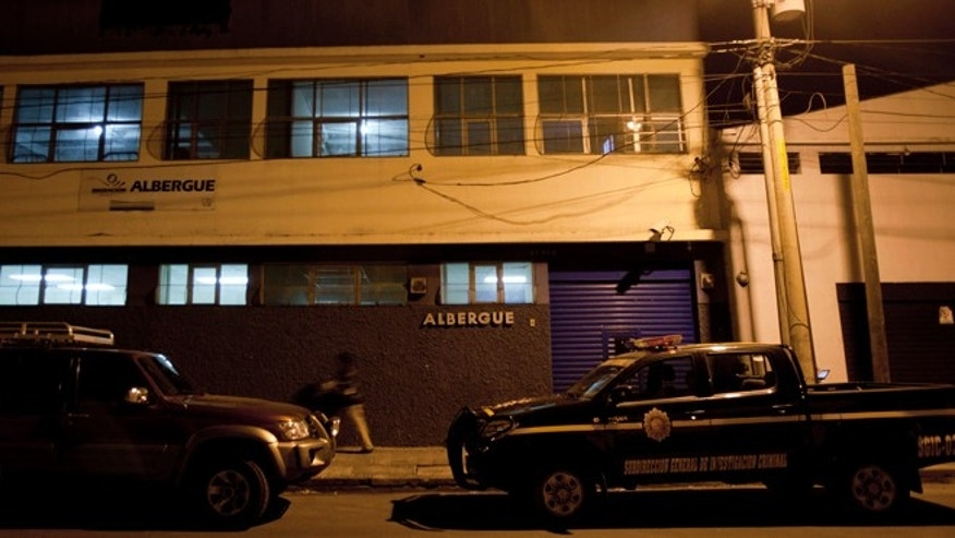 Dec. 5, 2012: A police vehicle parks outside a building used to house migrants who enter the country illegally, where software company founder John McAfee was taken in Guatemala City.