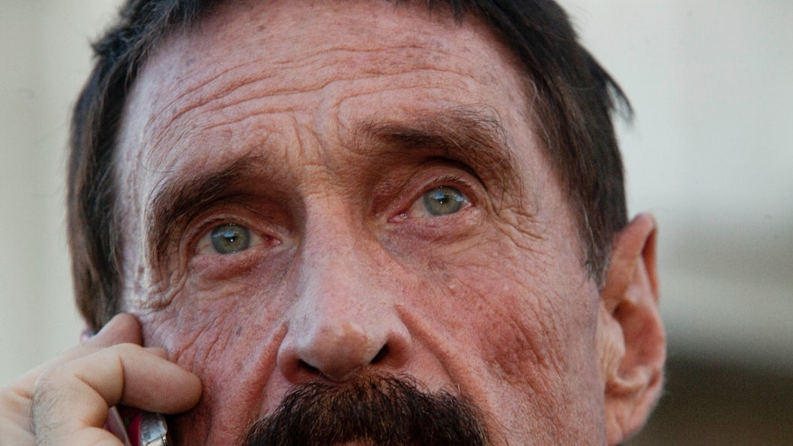 "Dec. 4, 2012: Software company founder John McAfee talks on his mobile phone after a press conference outside the Supreme Court in Guatemala City. McAfee, 67, has been identified as a ""person of interest"" in the killing of his neighbor in Belize, 52-year-old Gregory Faull."