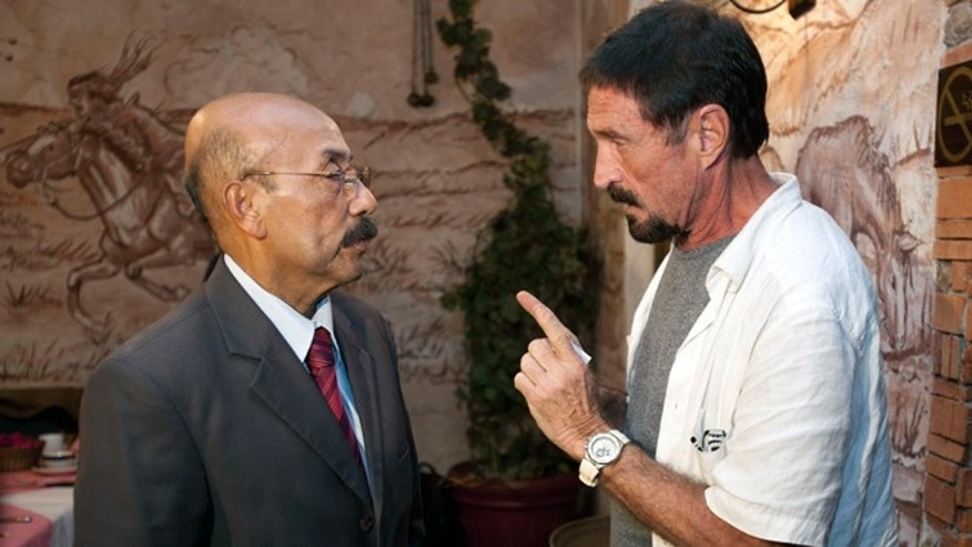 Dec. 4, 2012: Software company founder John McAfee talks to his lawyer Telesforo Guerra, right, after giving an interview at a local restaurant in Guatemala City.