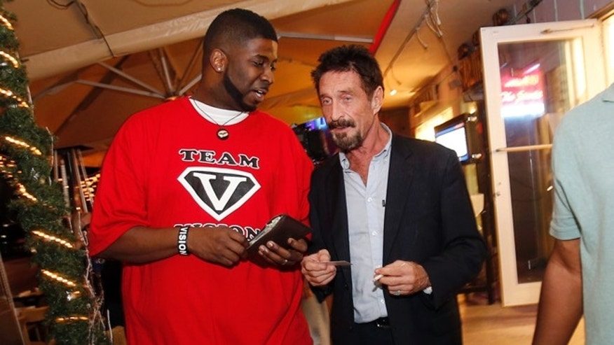 Dec 12, 2012: Anti-virus software founder John McAfee talks to an unidentified man as he walks on Ocean Drive in the South Beach area of Miami Beach, Fla., on his way to dinner. McAfee arrived in the U.S. on Wednesday night after being deported from Guatemala, where he had sought refuge to evade police questioning in the killing of a man in neighboring Belize.