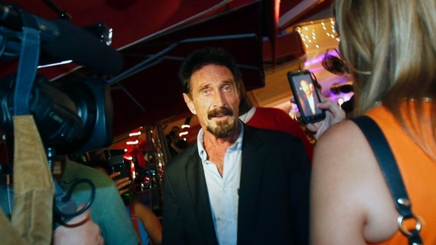 Dec 12, 2012: A television reporter takes a photo with her mobile phone of anti-virus software founder John McAfee, center, as he walks on Ocean Drive in the South Beach area of Miami Beach, Fla.