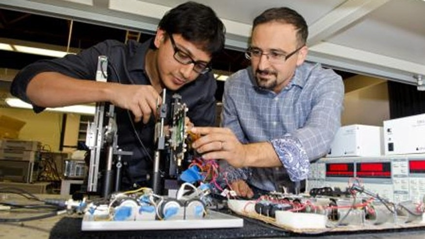 Caltech electrical engineers Kaushik Sengupta and Ali Hajimiri demonstrate their new terahertz imaging chip.