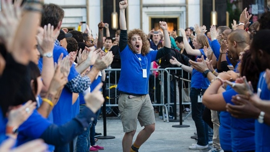Sept. 21, 2012: An Apple employee riles up his coworkers outside the Fifth Avenue Apple store to celebrate the release of the iPhone 5, in New York. Hundreds of people waited in line through the early morning to be among the first to get their hands on the highly anticipated phone.