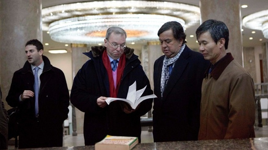"Jan. 9, 2013: Executive Chairman of Google, Eric Schmidt, second from left, and former Governor of New Mexico Bill Richardson, second from right,  look through an information technology text book at the Grand People's Study House in Pyongyang, North Korea. At left is director of Google Ideas think tank, Jared Cohen. The textbook is titled ""Aries Net+ Certified Technician First Edition Version 3.0."""
