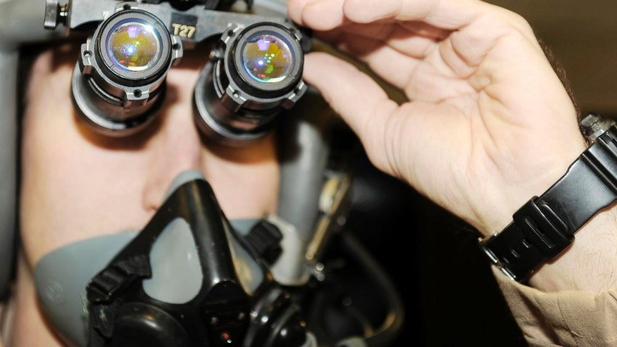 Jan. 4, 2010: Capt. David Snodgrass checks his night vision goggles before a mission at Bagram Airfield, Afghanistan.