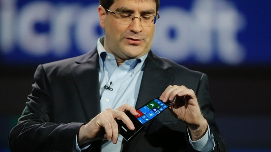 Jan. 9, 2013: Eric Rudder, chief technical strategy officer of Microsoft, holds a prototype Windows smartphone with a flexible OLED display during Samsung's keynote address at the International Consumer Electronics Show in Las Vegas.