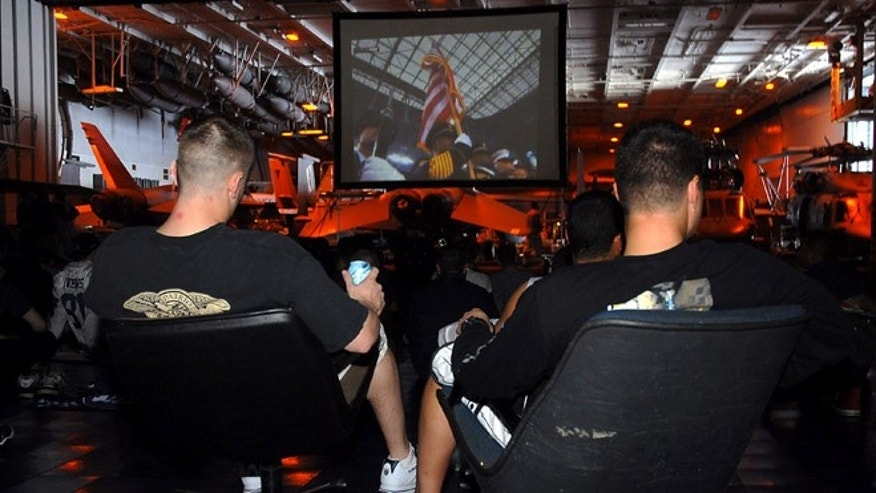 Sailors and Marines root for their teams while watching Super Bowl XLII in the hangar bay aboard the nuclear-powered aircraft carrier USS Nimitz (CVN 68) in 2008.
