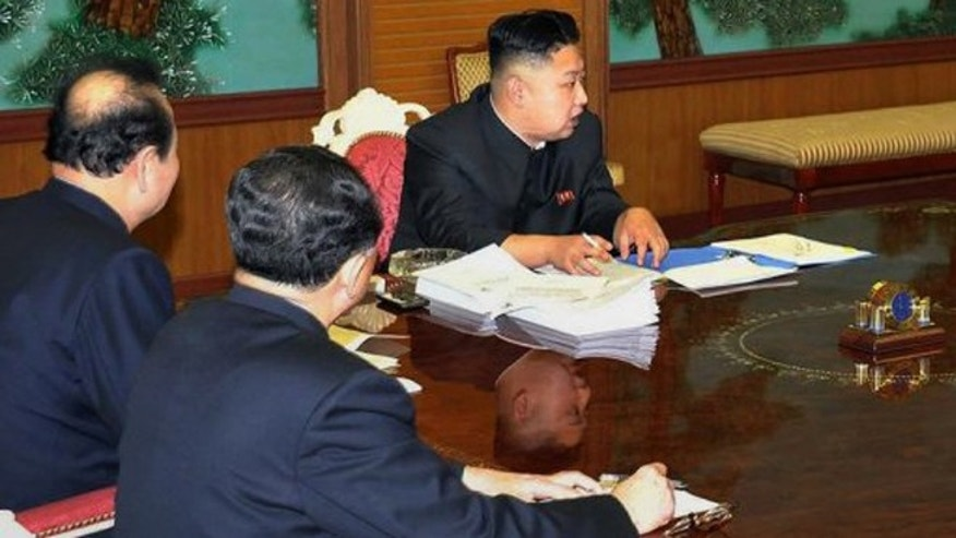 North Korean leader Kim Jong-Un (R) -- with a mysterious black smartphone on the table next to his right arm.
