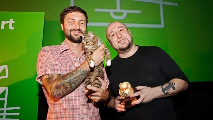 Aug. 30, 2012: Festival attendee Mike Bridavsky and his cat Lil Bub, left, pose with Golden Kitty Award-winner William Braden, at the Walker Art Center Internet Cat Video Festival in Minneapolis.
