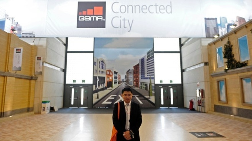 Feb. 26, 2013: A man stands up in front of a banner of Connected city at Mobile World Congress in Barcelona, Spain, where so-called machine-to-machine technology was all the buzz. Some analysts believe these types of connection will outgrow the traditional phone business in less than a decade.