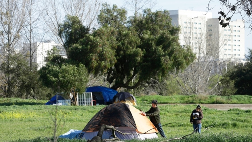 March 5, 2013: San Jose city workers Mark Ruffing, left, and Rita Tabaldo attach eviction notices to a tent at a tent city in San Jose, where food stamp participation just hit a 10 year high, African American wages fell 18 percent in two years and median incomes fell throughout the region.