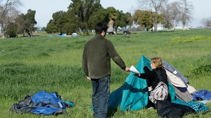 March 5, 2013: Kristina Erbenich, right, is handed an eviction notice by San Jose city worker Mark Ruffing at a tent city in San Jose, Calif. Simply put, while the ultra rich are getting even ultra richer, record numbers of Silicon Valley residents are slipping into poverty.