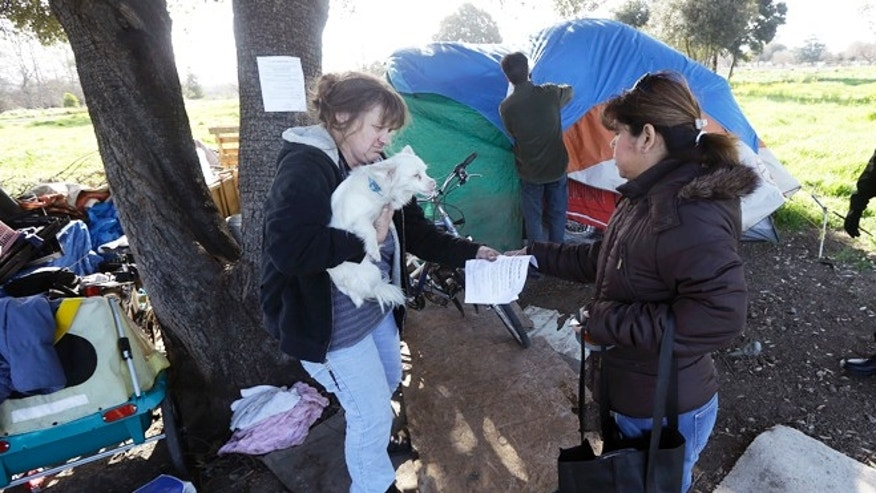 March 5, 2013: Wendy Clarke, left, holds her neighbor's dog Hero as she is handed an eviction notice by San Jose city worker Rita Tabaldo as city worker Mark Ruffing, center, attaches a notice to a Clarke's tent at a tent city in San Jose, Calif. Simply put, while the ultra rich are getting even ultra richer, record numbers of Silicon Valley residents are slipping into poverty.