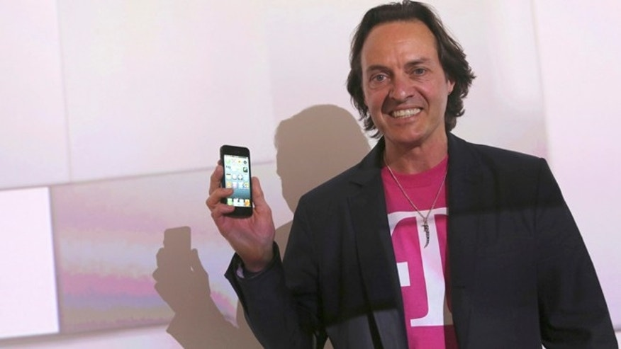 March 26, 2013: T-Mobile CEO John Legere sports an iPhone 5 and a grin during a news conference in New York.