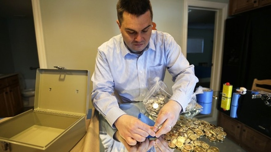 April 3, 2013: Mike Caldwell, a 35-year-old software engineer, looks over bitcoin tokens at his shop in Sandy, Utah. Caldwell mints physical versions of bitcoins, cranking out homemade tokens with codes protected by tamper-proof holographic seals.