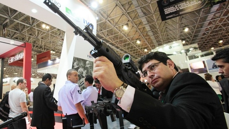 April 9, 2013: A man holds a Galil ACE 31 assault rifle at the Defence and Security International Exhibition Latin America Aero and Defence (LAAD) trade show in Rio de Janeiro.
