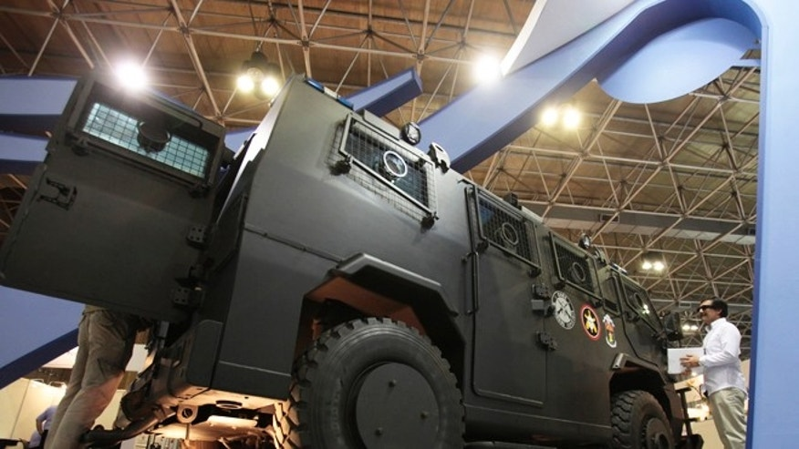 April 9, 2013: People check the Maverick, an internal security vehicle, at the Defence and Security International Exhibition Latin America Aero and Defence (LAAD) trade show in Rio de Janeiro .