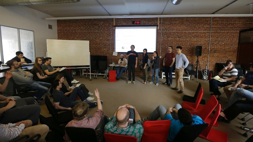 A group presents during a class at Dev Bootcamp in San Francisco, Tuesday, April 2, 2013. Dev Bootcamp is one of a new breed of computer-programming schools thats proliferating in San Francisco and other U.S. tech hubs. These hacker boot camps promise to teach students how to write code in two or three months and help them get hired as web developers, with starting salaries between $80,000 and $100,000, often within days or weeks of graduation. (AP Photo/Jeff Chiu)