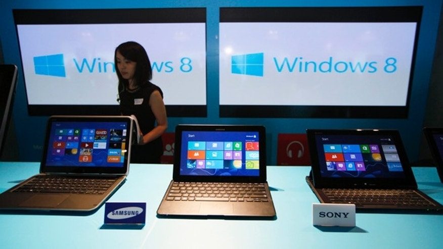 A woman walks past laptop computers running Microsoft Windows 8 operating system during its 2012 launch ceremony in Hong Kong.The company plans a line of small touch-screen devices powered by Windows, apparently intended to compete with 7-inch tablets like the iPad Mini and Amazon Kindle Fire.