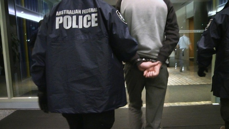 April 23, 2013: In this photo provided by the Australian Federal Police, a handcuffed man is escorted by police following his arrest on a charge of attacking and defacing a government website. The Australian man, who police say has claimed to be a high-level member of international hacking collective Lulz Security, was charged with two counts of unauthorized modification of data to cause impairment, and one count of unauthorized access to, or modification of, restricted data.