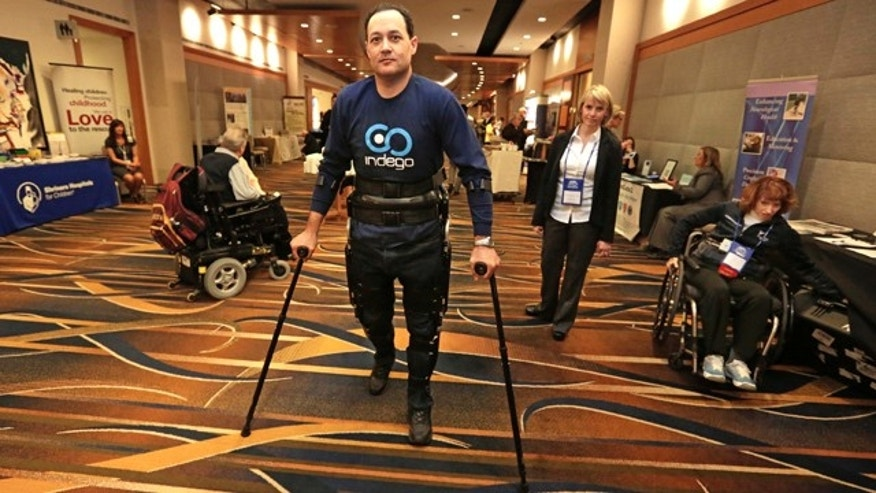 May 6, 2013: Michael Gore, center, who is paralyzed from a spinal injury, walks with the use of the Indego wearable robot under the supervision of physical therapist Clare Hartigan during a meeting of the American Spinal Injury Association at a downtown hotel in Chicago.