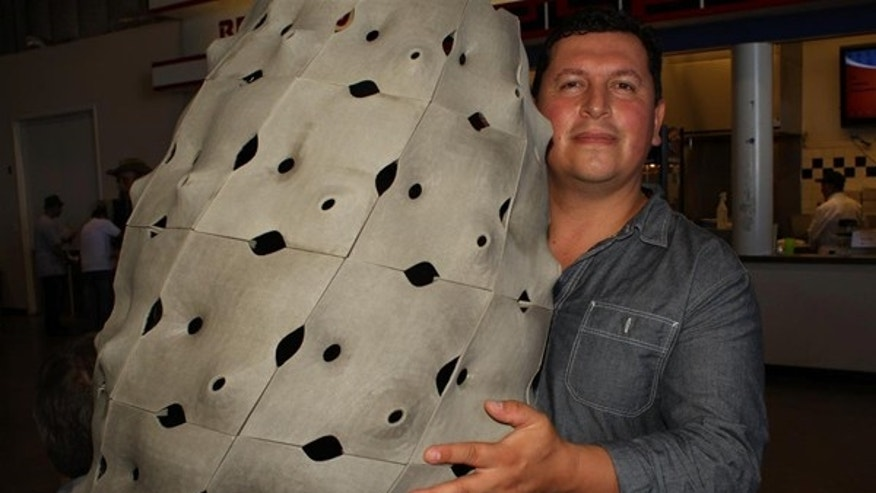 Ronald Rael holds an object created using a 3D printer and cement.