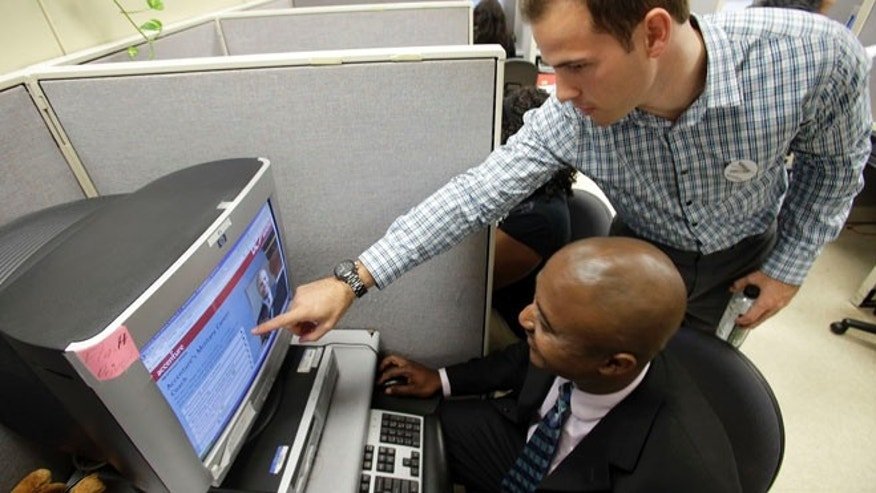 May 21, 2013: Accenture recruiter and military veteran, Chris Green points out an on-line tool for veterans like, Mark Scott of Charlotte looking for a job at the North Carolina Department of Commerce Division of Employment Security in Charlotte.