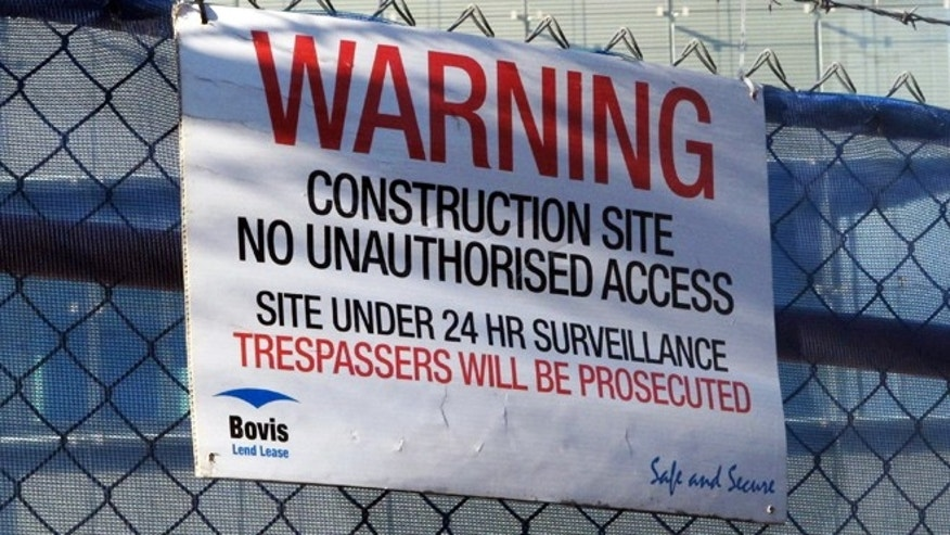 May 28, 2013: A warning sign hangs on a fence enclosing the Australian Security Intelligence Organization's new headquarters under construction in Canberra, Australia. Australian officials have refused to confirm or deny whether Chinese hackers had stolen the blueprints of the new spy agency building as a news report claims.